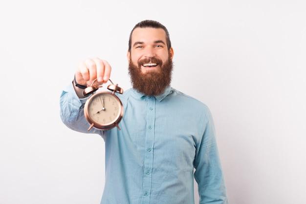 若いひげを生やした男がカメラに目覚まし時計を見せています。