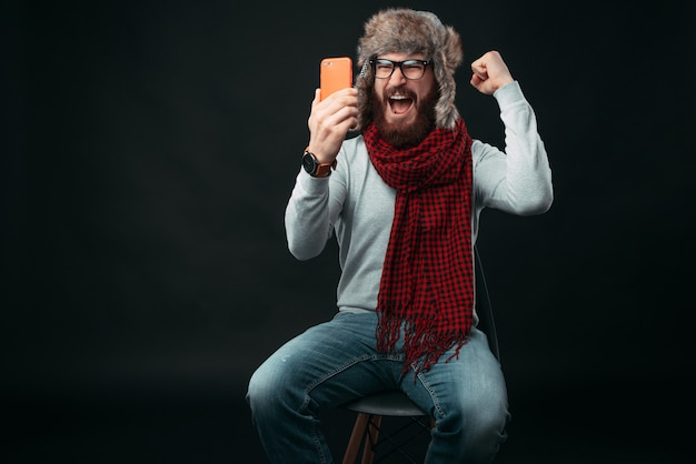 Young bearded man is wearing winter clothes, sitting on a chair in a studio, is screaming because he has won something on his phone.