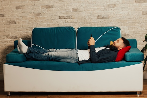 若いひげを生やした男は、自宅の青いソファに横になって電話を見ています。