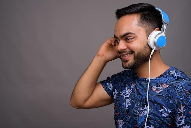 灰色に対して音楽を聴く若いひげを生やした男