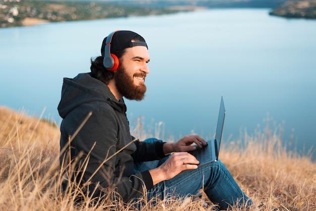 音楽を聴いて、川の近くのフィールドでコンピューターで作業している若いひげを生やした男