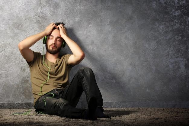 수염 난 젊은이 회색 벽에 앉아 헤드폰으로 음악을 듣는