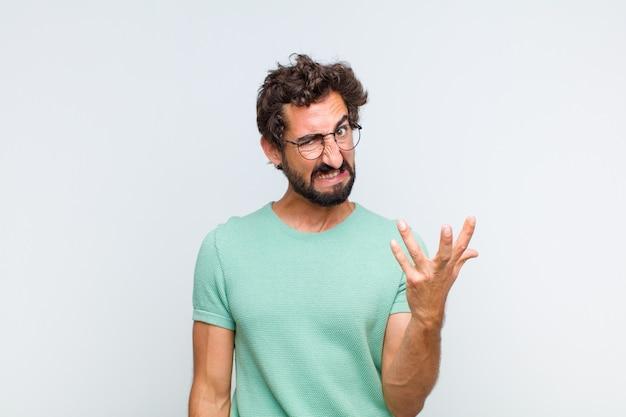 Молодой бородатый мужчина выглядит сердитым, раздраженным и расстроенным, кричит, черт возьми, или что с тобой не так