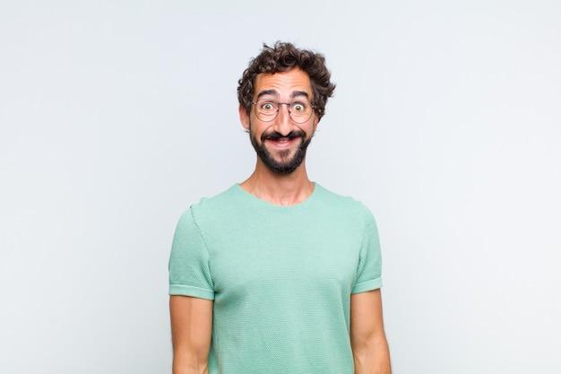 Молодой бородатый мужчина выглядит счастливым и глупым, с широкой веселой сумасшедшей улыбкой и широко открытыми глазами