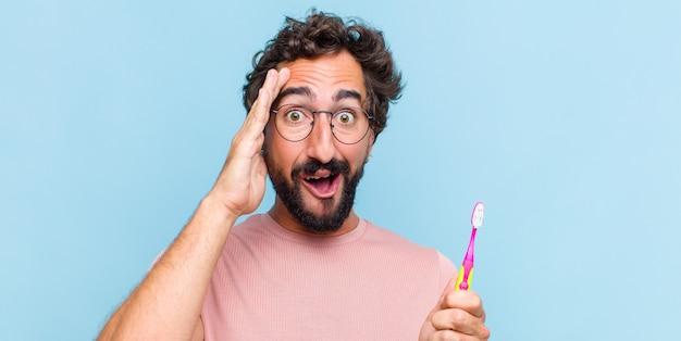 젊은 수염 난 남자는 행복하고, 놀랐고, 놀랐고, 웃고, 놀랍고 놀라운 좋은 소식을 깨닫고 있습니다.