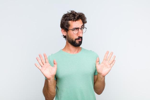 Молодой бородатый мужчина выглядит нервным, встревоженным и обеспокоенным, говорит, что не моя вина, или что я этого не делал.