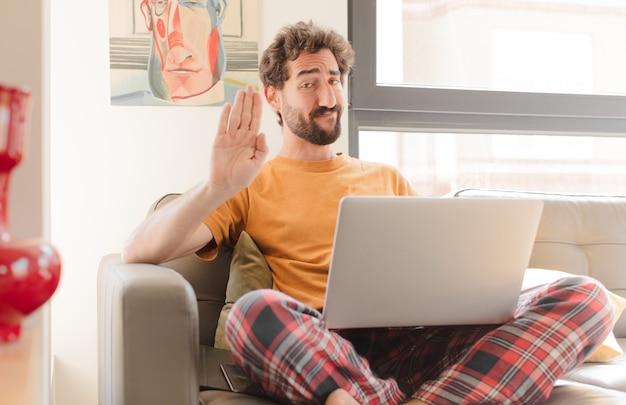 Молодой бородатый мужчина выглядит серьезным, суровым, недовольным и злым, показывая открытую ладонь, делая жест остановки и сидя с ноутбуком