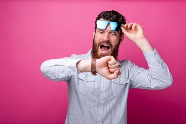 Молодой бородатый человек, глядя в шоке на его часы, подняв его очки на розовом фоне.