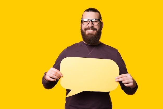 Young bearded man looking and smiling at the camera is holding a speech bubble near a yellow wall