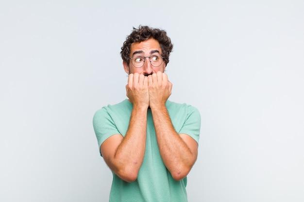 Молодой бородатый мужчина выглядит встревоженным, встревоженным, напряженным и напуганным, кусает ногти и смотрит в пространство для боковой копии
