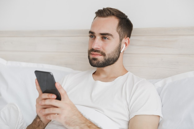 Young bearded man lying in bed with white sheet pillow blanket in bedroom at home