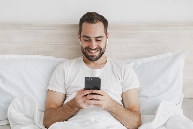 집에서 침실에 흰색 시트 베개 담요와 침대에 누워있는 젊은 수염 난된 남자