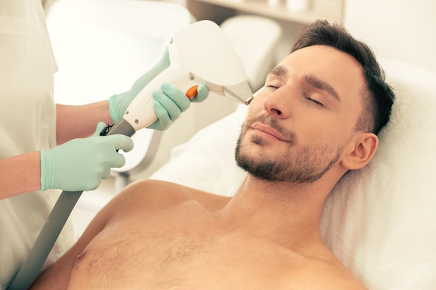 Young bearded man lying on the pillow with closed eyes and professional cosmetologist removing hair on his face with laser hair removal tool