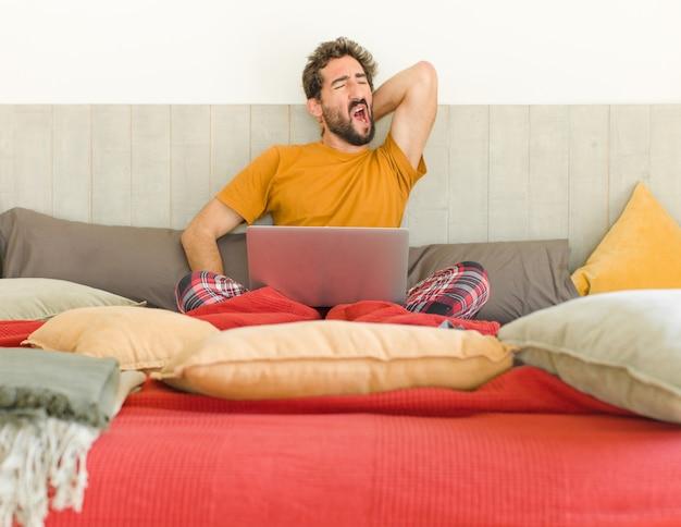 노트북으로 침대에 젊은 수염 된 남자