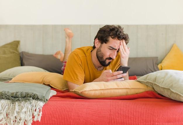 그의 휴대 전화와 함께 침대에 젊은 수염 된 남자