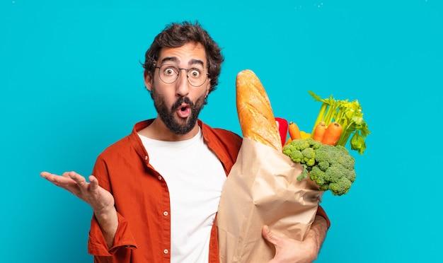 턱수염을 기른 젊은 남자가 입을 벌리고 놀라고, 충격을 받고, 믿을 수 없는 놀라움과 야채 가방을 들고 놀랐습니다.