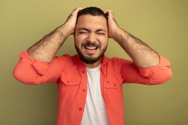 Giovane uomo barbuto in camicia arancione pazzo pazzo gridando e urlando con la mano sulla sua testa in piedi sopra la parete chiara