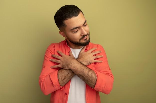 Giovane uomo barbuto in camicia arancione che tiene le mani incrociate sul petto con gli occhi chiusi sentendosi grato in piedi sopra il muro di luce