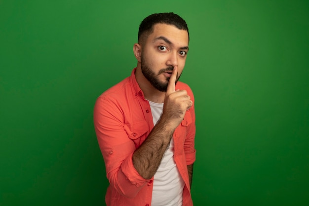 Giovane uomo barbuto in maglietta arancione che fa gesto di silenzio con il dito sulle labbra in piedi sopra la parete verde