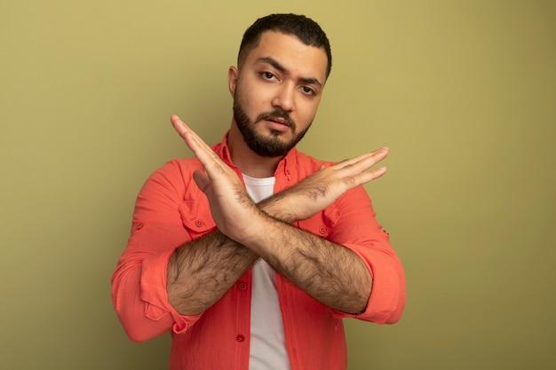 Giovane uomo barbuto in maglietta arancione che fa gesto di arresto incrociando le mani con la faccia seria in piedi sopra la parete leggera