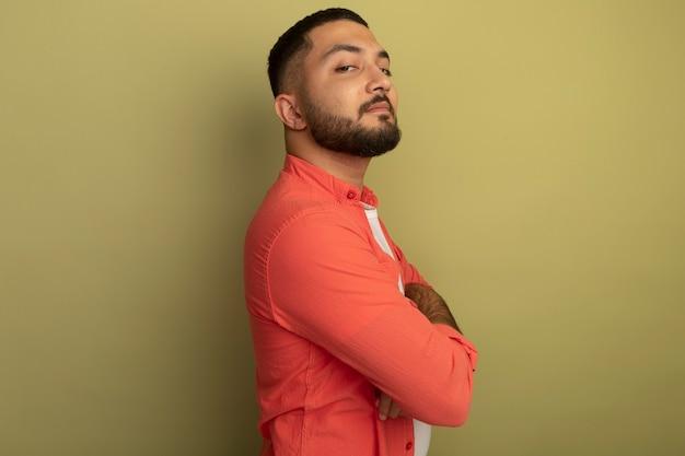 Giovane uomo barbuto in maglietta arancione in piedi lateralmente con le braccia incrociate guardando fiducioso sulla parete leggera