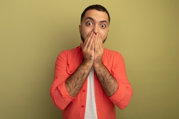 Giovane uomo barbuto in camicia arancione sorpreso che copre la bocca con le mani in piedi sopra la parete chiara