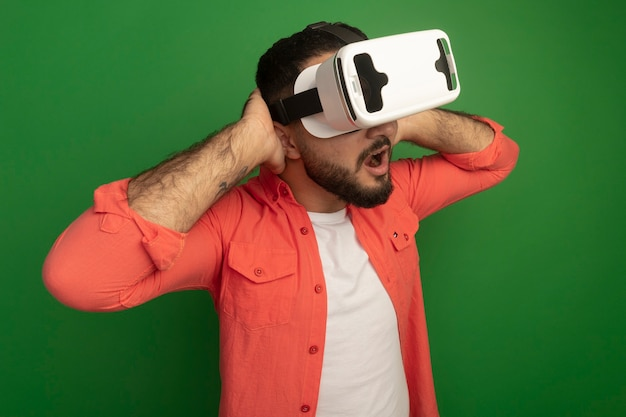 Young bearded man in orange shirt with virtual reality glasses amazed and surprised with hands behind his head standing over green wall