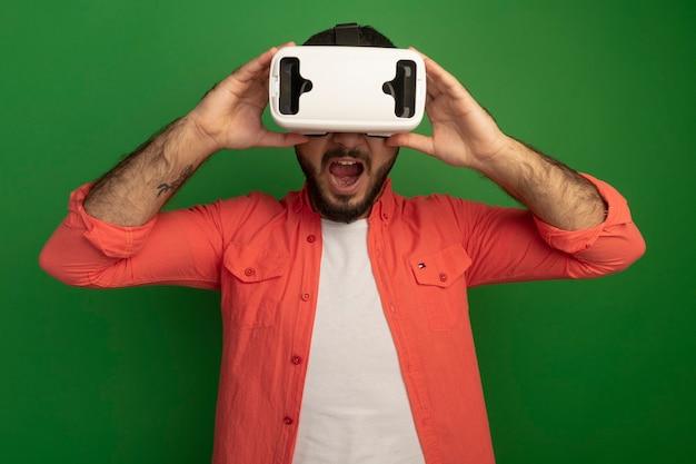 Giovane uomo barbuto in camicia arancione con occhiali per realtà virtuale eccitato in piedi sopra la parete verde