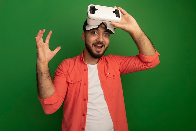 Young bearded man in orange shirt with virtual reality glasses on his head  raising arm amazed and surprised standing over green wall