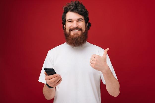 Молодой бородатый человек над красной стеной держит смартфон счастливым с большой улыбкой делает хорошо знаком, большой палец вверх