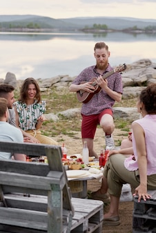 友人がテーブルの周りに座って、湖の近くの美しい夏の夜に食事をしたり話したりしながらギターを弾く若いひげを生やした男