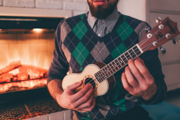 Young bearded man playing ukulele in room at fireplace