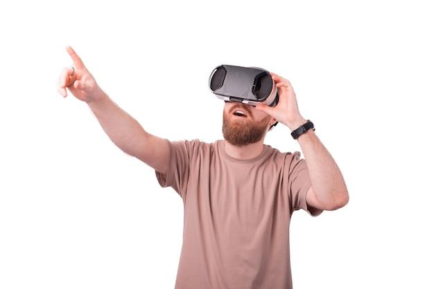 Молодой бородатый мужчина указывая в сторону и в очках vr, опыт виртуальной реальности