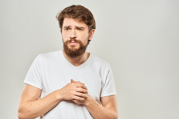 Young bearded man posing against against the grey wall
