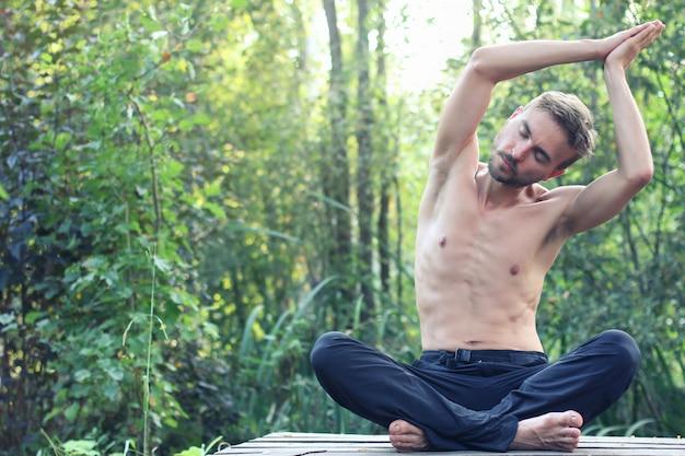 젊은 수염 남자 연습 요가 야외. 배경에 녹색 숲