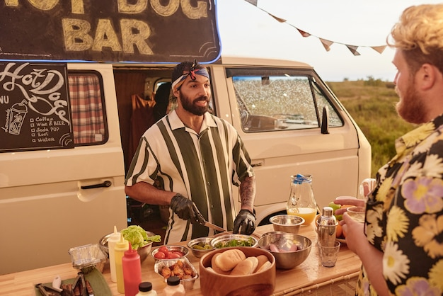 Young bearded man preparing sandwiches for customer at outdoor party