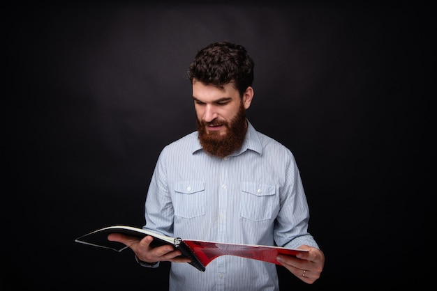 Young bearded man reading a magazine or a book standing in a black studio.
