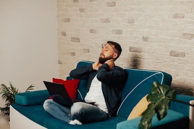 노트북으로 편안한 소파에 편안한 젊은 수염 남자. 진정 남자 라운지 눈은 노트북에서 열심히 일한 후 휴식을 취합니다.