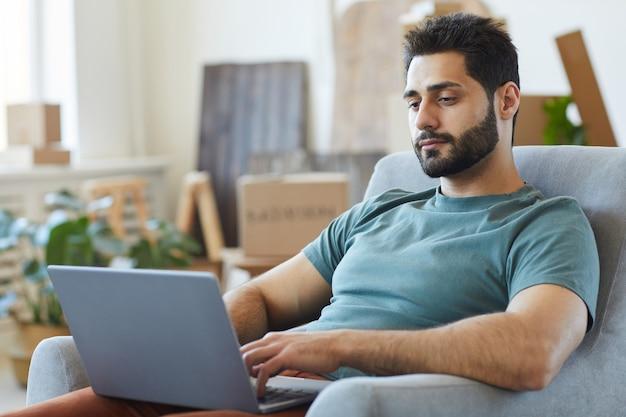 自宅の部屋でラップトップコンピューターと肘掛け椅子で休んでいる若いひげを生やした男