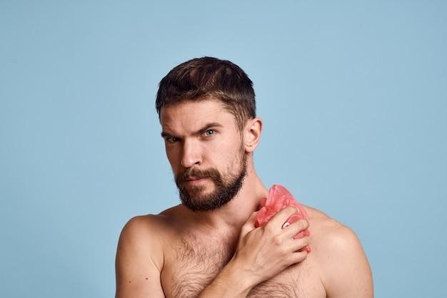 若いあごひげを生やしたバススポンジでこすり