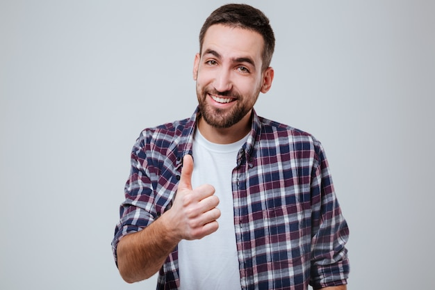Giovane uomo barbuto in camicia che mostra pollice in su