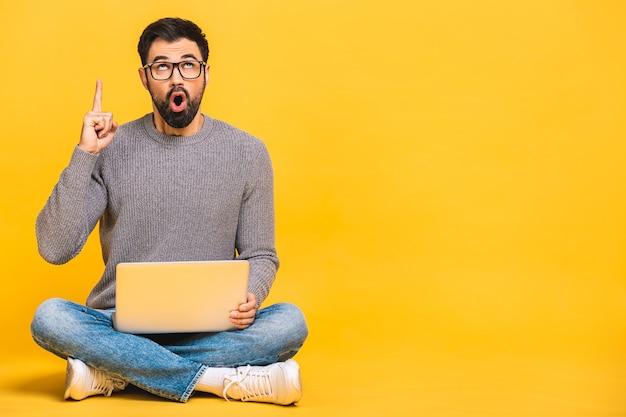 Молодой бородатый мужчина потрясен удивлен удивлен портативным компьютером. смешное изображение молодой кавказской модели студента, сидя на полу