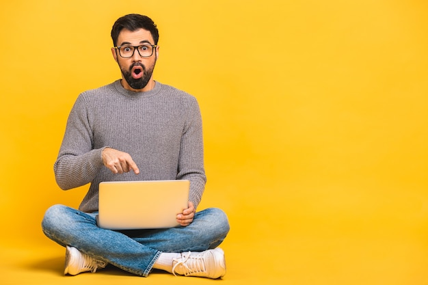 Young bearded man shocked surprised amazed with laptop computer. funny image of young caucasian male student model sitting on floor