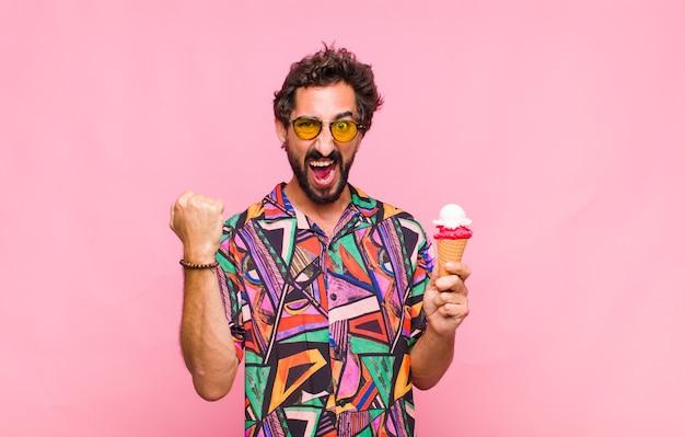 Молодой бородатый мужчина агрессивно кричит с гневным выражением лица или со сжатыми кулаками празднует успех