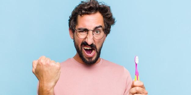 Молодой бородатый мужчина агрессивно кричит с гневным выражением лица или со сжатыми кулаками, празднуя успех