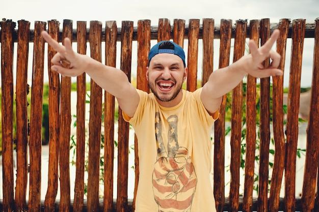 Молодой бородатый мужчина показывает жест мира и улыбается у деревянного забора