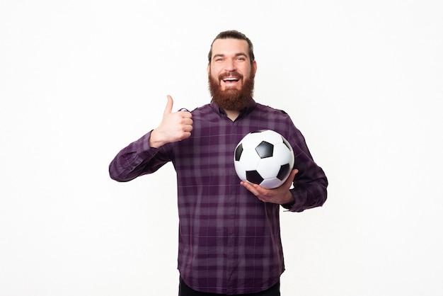 Молодой бородатый мужчина показывает палец вверх и держит футбольный мяч