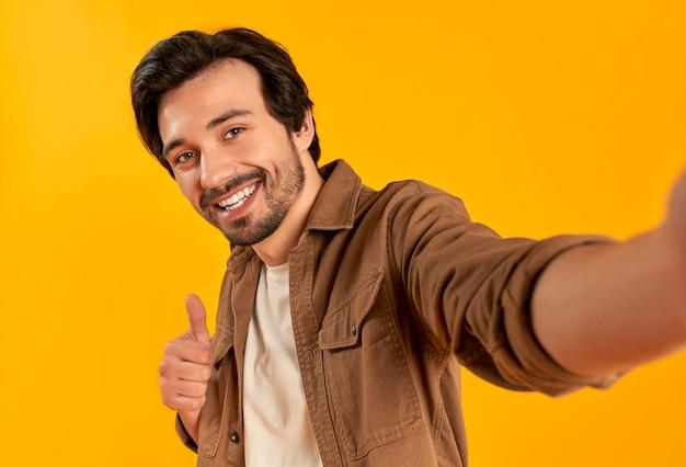 Молодой бородатый мужчина показывает палец вверх жестом и делает селфи фото на смартфоне, улыбаясь изолированно.