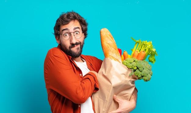 턱수염을 기른 젊은 남자가 어깨를 으쓱하고 혼란스럽고 불확실하다고 느끼며 팔짱을 끼고 어리둥절한 표정으로 의심하고 야채 가방을 들고 있다