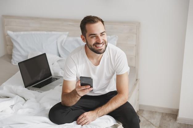 젊은 수염 난된 남자는 집에서 침실에 흰색 시트 베개 담요와 침대에 앉아